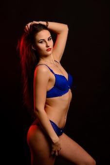 Sexy moda brunetka kobieta o długich ciemnych włosach w niebieskiej bieliźnie