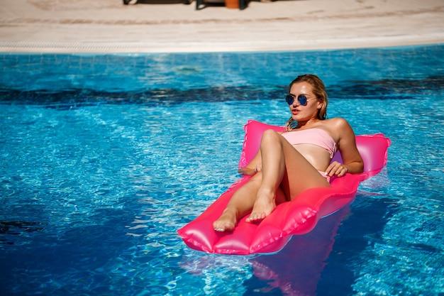 Sexy modelki odpoczynek i opalanie na materacu w basenie. kobieta w różowym stroju kąpielowym bikini unoszącym się na dmuchanym różowym materacu. spf i krem do opalania