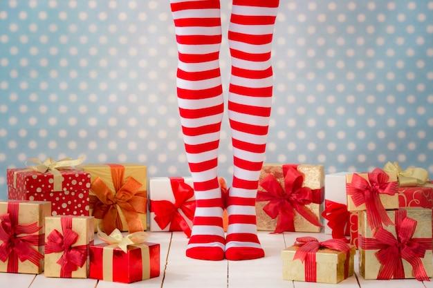 Sexy nogi kobiety santa. koncepcja zakupów świątecznych. świąteczne pudełko na prezent