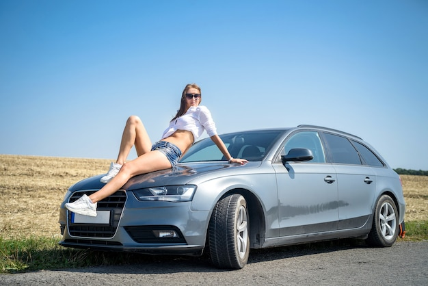 Sexy piękna kobieta, leżąc na masce samochodu w białej koszuli i krótkich dżinsach. ciesz się na drodze
