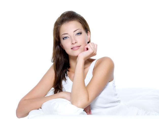 Sexy piękna kobieta z czystej skóry siedzi na kanapie - na białym tle