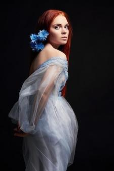Sexy piękne rude dziewczyny z długimi włosami w bawełnianej sukience retro. portret kobiety na czarnym tle. głębokie oczy. naturalne piękno, czysta skóra, pielęgnacja twarzy i włosów. mocne i gęste włosy. kwiat