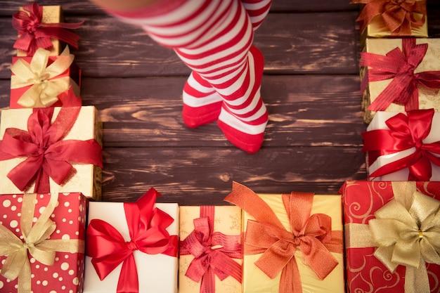 Sexy santa kobieta nogi i pudełka na prezenty. koncepcja święta bożego narodzenia. widok z góry