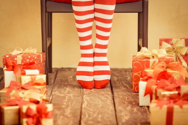 Sexy santa kobieta nogi i pudełka na prezenty. świąteczna koncepcja świąteczna