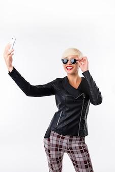 Sexy szczęśliwa kobieta z czerwonymi ustami, biorąc zdjęcie selfie