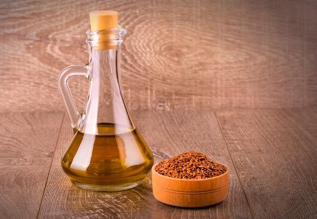Sezamowi ziarna w pucharze i butelce olej z korkiem na drewnianym stole
