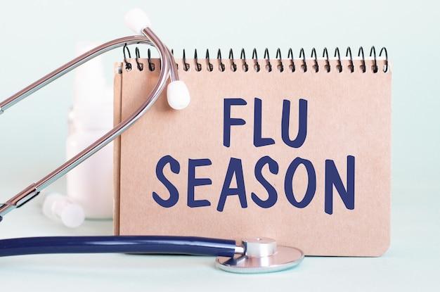 Sezon grypowy - diagnoza zapisana na białej kartce papieru. stetoskop i białe butelki medycyny w tle. pojęcie medyczne. selektywna ostrość