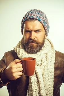 Sezon jesień lub zima napoje i koncepcja wypoczynku przystojny mężczyzna w kapeluszu i szaliku trzyma kubek