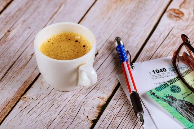 Sezon podatkowy biuro ze szklanką i długopisem na formularzu zeznania podatkowego 1040 z czarną kawą