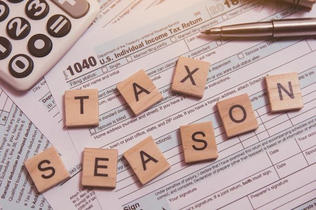 Sezon podatkowy z drewnianymi klockami alfabetu, kalkulator, długopis na formularzu podatkowym 1040