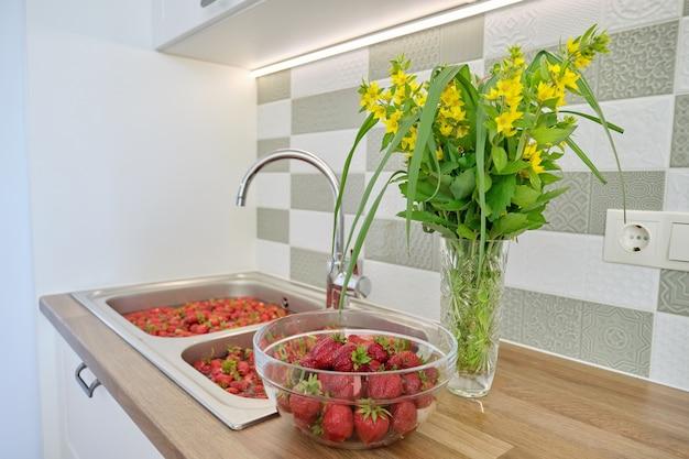 Sezon truskawkowy, mycie jagód w wodzie w umywalce w domowej kuchni. dużo truskawek, przygotowanie jagód na dżem, do zamrożenia