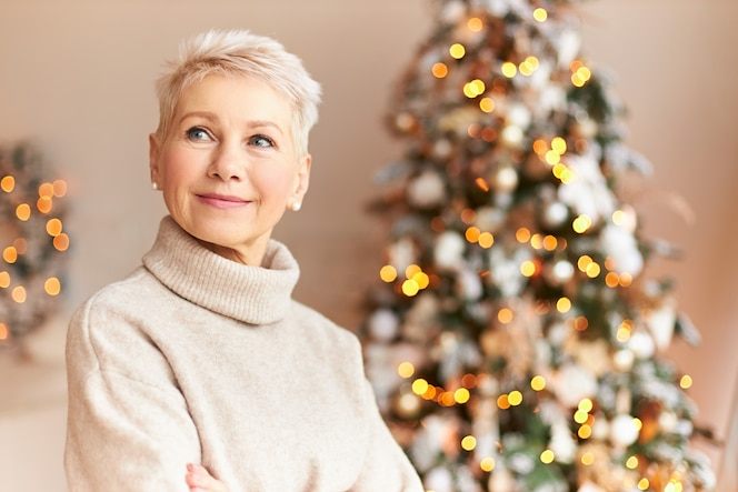 Sezon wakacyjny, tradycja i koncepcja świętowania. atrakcyjna sześćdziesięcioletnia kobieta w przytulnym swetrze stojąca w salonie ozdobiona majestatyczną choinką z ozdobami, girlandami i lampkami