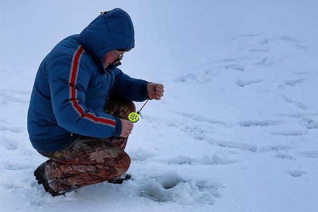 Sezon zimowy staruszek łowiący ryby na jeziorze