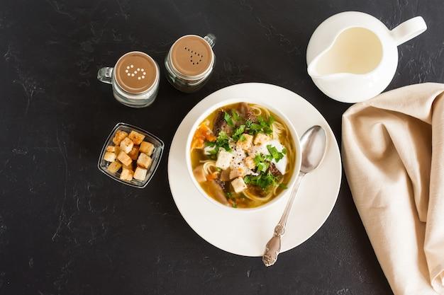 Sezonowa letnia zupa z leśnych grzybów ze śmietaną, zieleniną i grzankami. pyszny obiad. czarne tło. widok z góry.