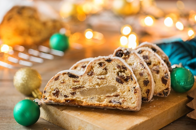 Sezonowe jedzenie i picie, koncepcja zima. tradycyjne europejskie niemieckie domowe ciasto świąteczne, ciasto deserowe stollen na drewniane tła z świąteczną dekoracją.