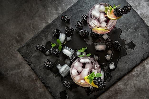 Sezonowe napoje bezalkoholowe. pragnienie w upalny letni czas. dwie szklanki lodu, wody, limonki i jagód morwy z miętą. dieta ketonowa, napoje bezalkoholowe i napoje alkoholowe. koktajl owocowy