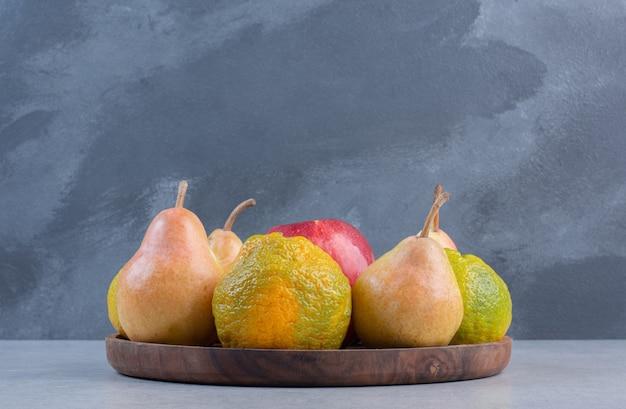Sezonowe owoce na drewnianym talerzu na szarym tle.