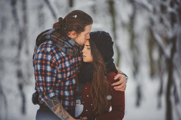 Sezonowe zajęcia na świeżym powietrzu para spaceru w śnieżnym lesie zimą