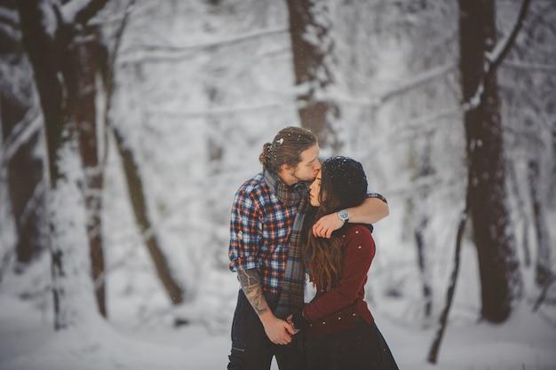 Sezonowe zajęcia na świeżym powietrzu. styl życia uchwycić miłości para spaceru w śnieżnym lesie zimą