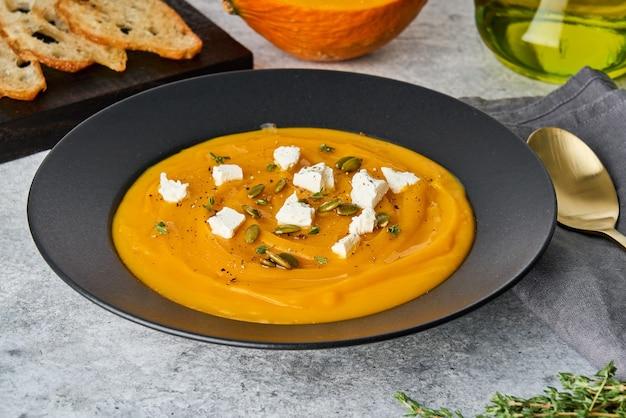 Sezonowy krem z puree z dyni z grzanką tymiankową z pestkami sera feta i oliwą z oliwek