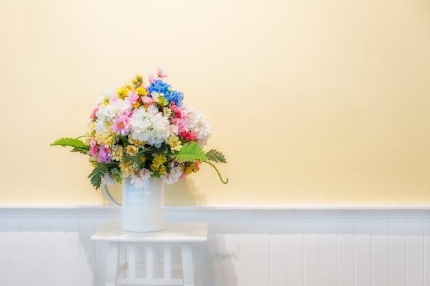 Sfałszowani kwiaty dla wewnętrznej dekoraci na białym drewnie z śmietanki ścianą w tle.