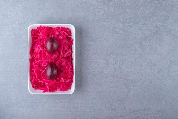 Sfermentowana czerwona kapusta leży i śliwka w misce