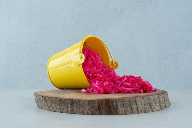 Sfermentowana czerwona kapusta z żółtego wiadra na kawałku drewna.
