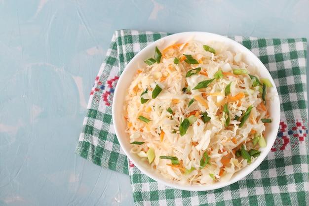 Sfermentowana żywność, domowa kapusta kiszona z marchewką i zieloną cebulą w misce na jasnoniebieskiej powierzchni, widok z góry, miejsce na kopię