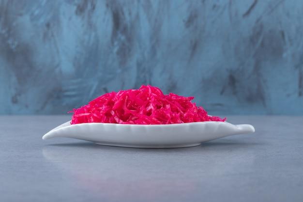 Sfermentowana żywność. kapusta kiszona w fantazyjnym naczyniu, na marmurowym tle.