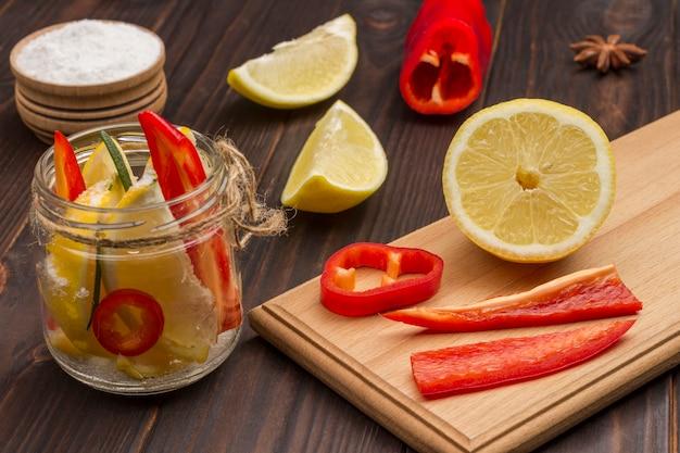 Sfermentowane cytryny z solą w słoikach i papryczką chili na desce do krojenia. naturalny środek wzmacniający odporność. widok z góry. ścieśniać