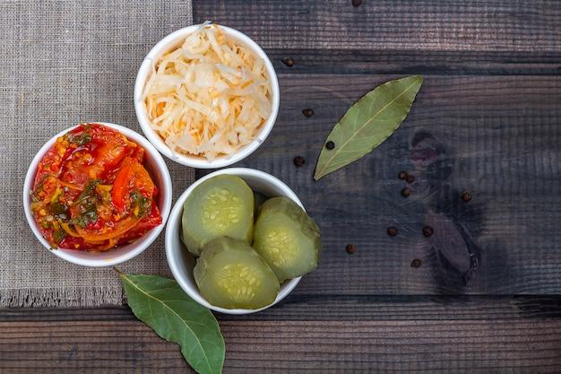 Sfermentowane warzywa, kapusta kiszona, słone konserwowe ogórki, ogórki i pomidory. na rustykalne drewniane tła. zdrowe odżywianie. organiczne wegetariańskie jedzenie
