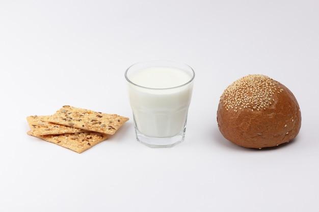 Sfermentowany napój kefirowy w szklance. kefir i chleb na białym tle. jogurt i kromka chleba