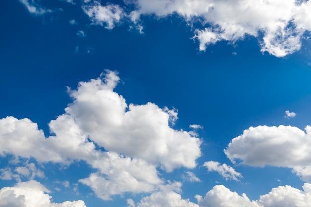 Sfotografowane z bliska białe chmury są na niebieskim niebie, płytkiej głębi ostrości