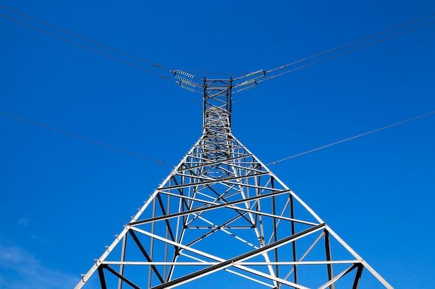 Sfotografowane z bliska słupy elektryczne wysokiego napięcia znajdujące się na wsi