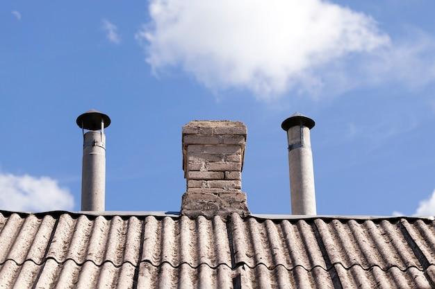 Sfotografowane zbliżenie fragmentu dachu znajdującego się na nim prywatnego budynku z rurami do ogrzewania