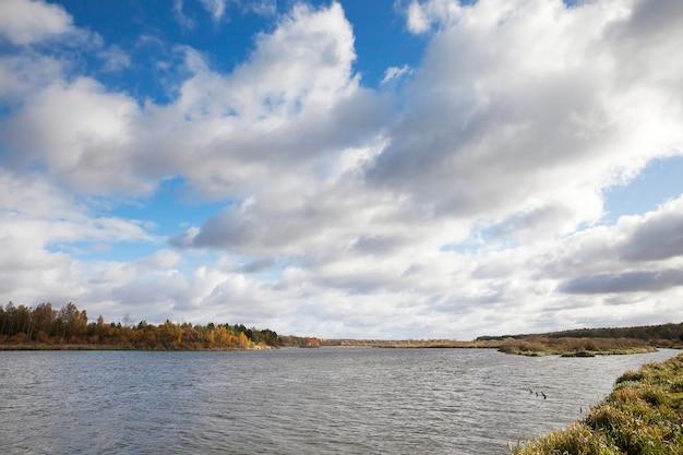 Sfotografowano rzekę niemen, położoną na białorusi, sezon jesienny, las i drzewa żółkły w pochmurną pogodę