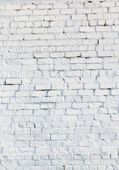 Sfotografowany zbliżenie starej ściany budynku z cegieł pomalowanych na biało