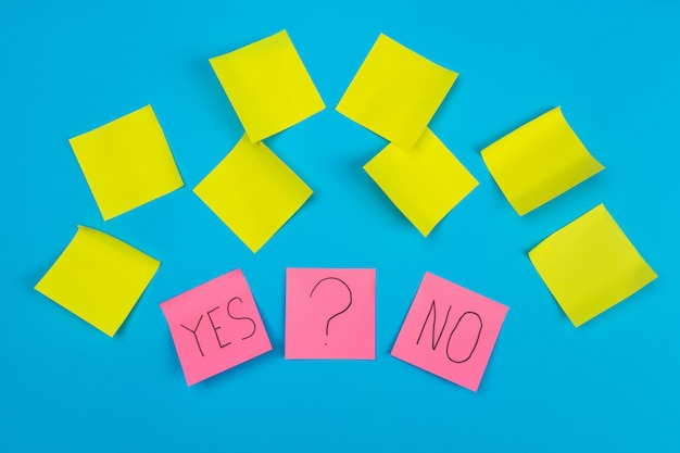 Sfotografuj dwie różowe naklejki z frazą tak lub nie oraz naklejkę ze znakiem zapytania na niebiesko z żółtymi samoprzylepnymi naklejkami. artykułów biurowych.