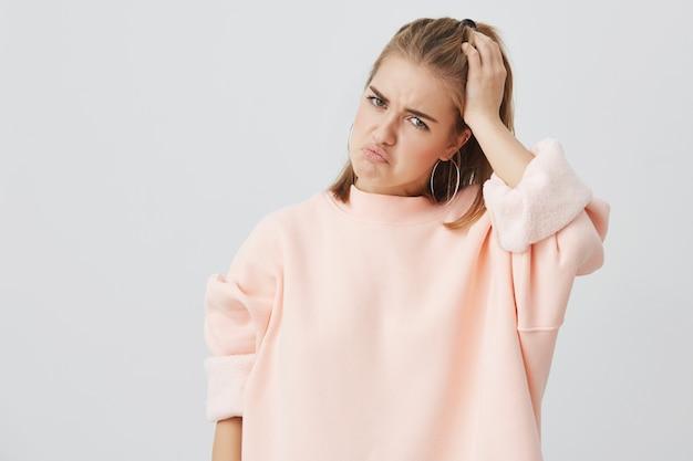 Sfrustowana młoda caucasian kobieta ubierająca w menchiach ma ból głowy utrzymuje rękę na głowie marszczy brwi twarz z bólem patrzeje nieszczęśliwym. żeński uczeń w rozpaczy ma stresującą sytuację na uniwersytecie