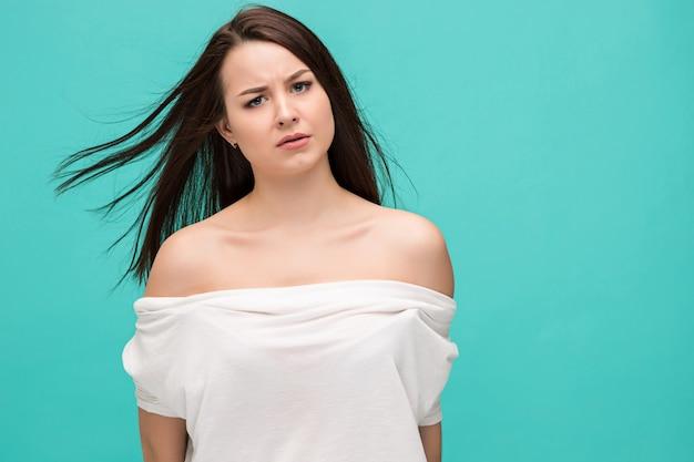 Sfrustowana młoda kobieta pozuje na błękicie