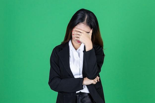 Sfrustowany zaakcentowany młody azjatykci bizneswoman z ręką na twarzy
