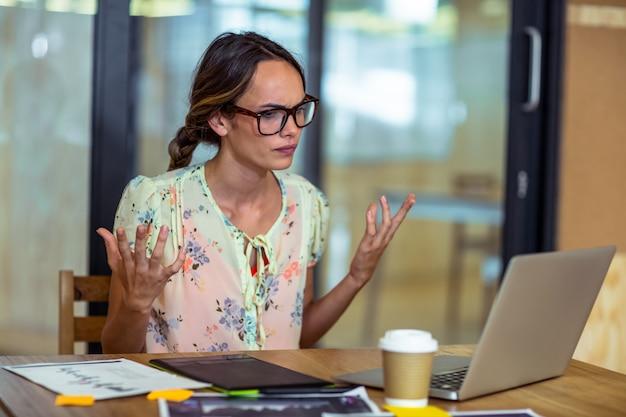 Sfrustowany żeński projektant graficzny patrzeje laptop