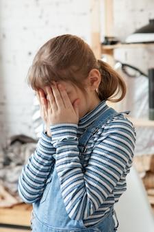 Sfrustrowana 8-letnia blond dziewczyna zakrywająca twarz