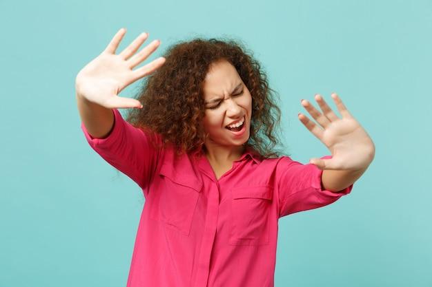Sfrustrowana afrykańska dziewczyna stojąca z wyciągniętymi rękami, pokazując gest stop z palmami na białym tle na niebieskim tle ściany turkus. ludzie szczere emocje, koncepcja stylu życia. makieta miejsca na kopię.