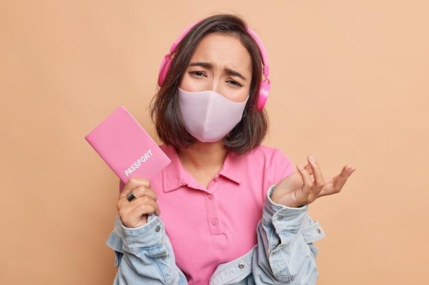 Sfrustrowana azjatka czuje się nieszczęśliwa, ponieważ nie może podróżować za granicę, nosi maskę higieniczną chroniącą przed koronawirusem, nosi zwykłe ubrania, chce odbyć podróż