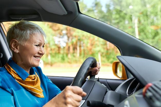 Sfrustrowana dojrzała kobieta krzywi się, ma nieszczęśliwe spojrzenie, siedzi w samochodzie w oparzeniach kierowcy, jest zestresowana, ponieważ na środku drogi skończyła się jej benzyna.
