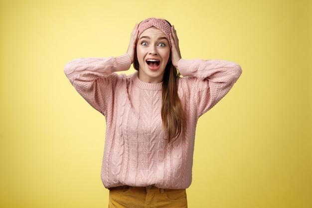 Sfrustrowana dziewczyna w panice krzyczy chwytając się za głowę krzyczy zmartwiona i przerażona wpatrując się w wyłupiaste oczy...