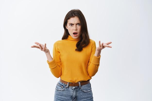 Sfrustrowana i zdezorientowana młoda kobieta, podnosząca ręce i wskazująca na coś złego, narzekająca i marszcząca brwi, stojąca zatroskana o białą ścianę