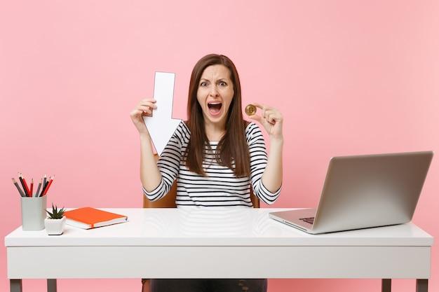Sfrustrowana kobieta krzyczy, przytrzymując bitcoin strzałki wartości spadku wartości, metalowa moneta w złotym kolorze, przyszła praca walutowa z laptopem pc na białym tle na różowym tle. osiągnięcie kariery biznesowej. skopiuj miejsce.