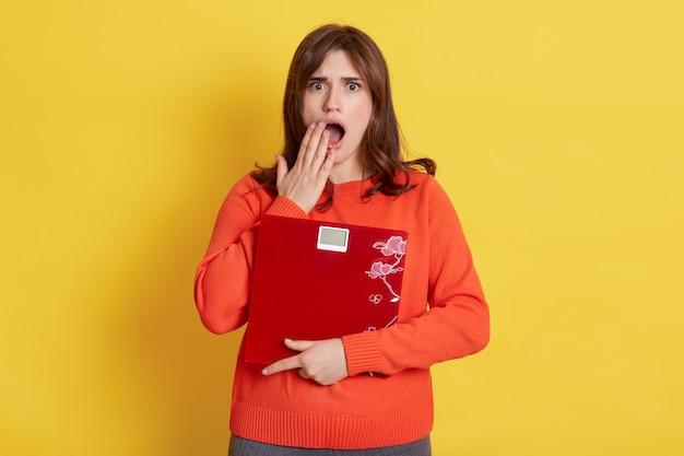 Sfrustrowana kobieta ze skalą w dłoniach, pozująca na żółtym tle, bardzo zszokowana